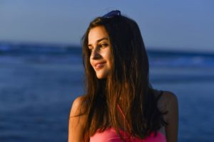 夏の夕暮れの海で陽を浴びている外国人女性のアップ