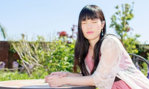 庭のイスに座ってまぶしそうにこちらを見ている日本人女性