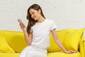 黄色いソファとクッションでスマホをいじっている女性