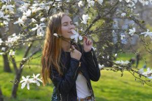 春の外出で白い花のにおいを嗅いでいる外国人美女