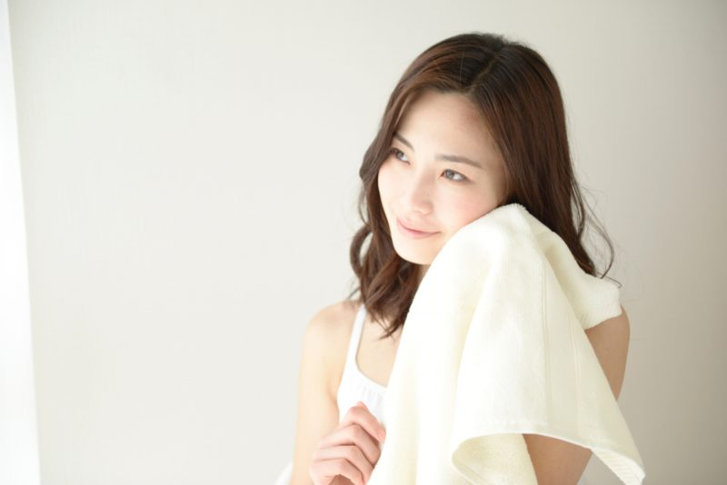 タオルを頬に当てている女性の画像
