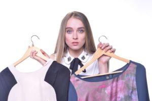 どちらの服にしようかと選びながら驚いている外国人女性