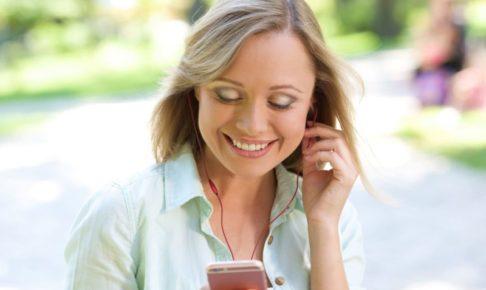 夏の公園でスマホで音楽を聴いて楽しんでいる女性