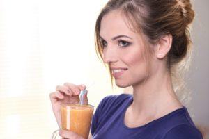 キリッとしながらジュースを飲んでいる外国人女性