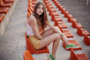 オレンジのスタジアムの席で座っている外国人女性