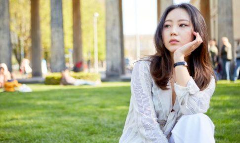 大学の屋外の芝生の上で物思いの深けているアジア人美女