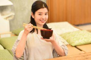 味噌汁の椀を持っている女性