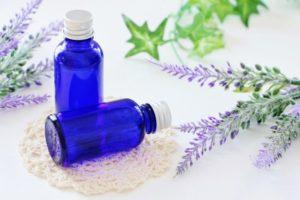 ラベンダーの花と一緒に置いてある青い化粧瓶二つ