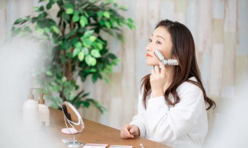 鏡の前で美顔ローラーを使ってマッサージする女性