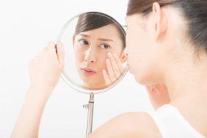 手鏡で目もとのたるみを気にする女性