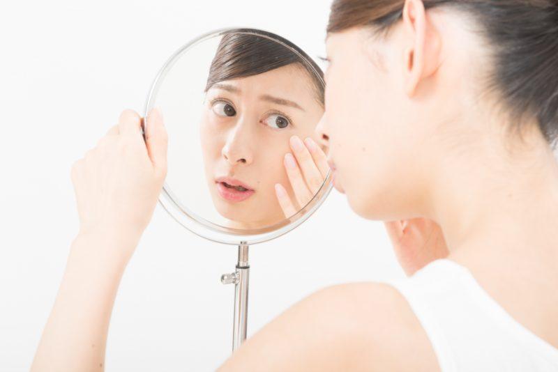 鏡を見て肌トラブルに悩む女性