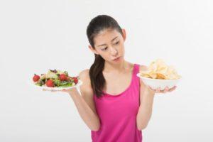 野菜とポテチを手に持っている女性