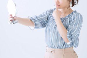 自分の鼻が気になり鏡で見ている青いブラウスの女性