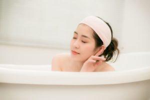 ヘアバンドを巻いて気持ち良さそうに入浴している女性