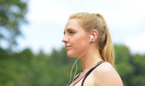 青空の下で運動中の女性が音楽を聴いているところ