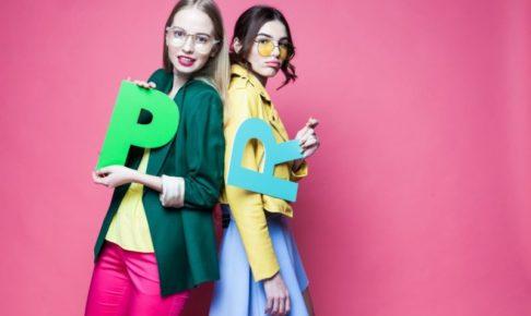 ピンクの背景の中PとRの文字を持っている二人の女性