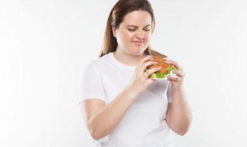 ハンバーガーを持って食べようとしている太めの女性