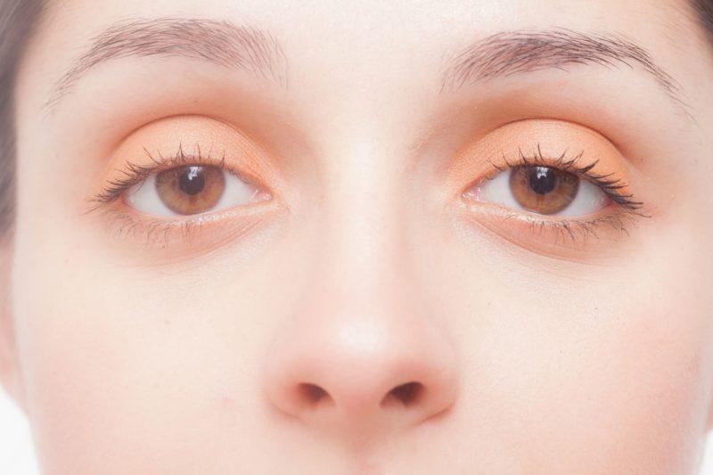 オレンジのアイシャドウをして目を見開いている女性のアップ