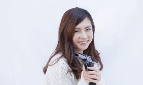 笑顔で銃を構える女性