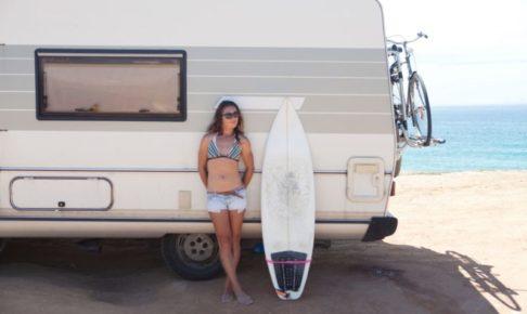 ワゴンの日陰のところに避難している女性サーファー