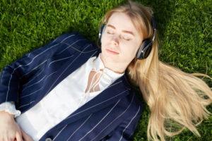 ヘッドホンをしながら芝生の上でうたた寝する白人女性