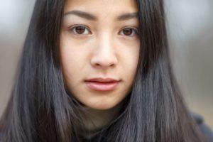 黒い長い髪の女性のキッとした表情のアップ