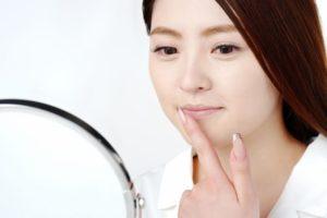 鏡で唇の状態を触ってみる女性