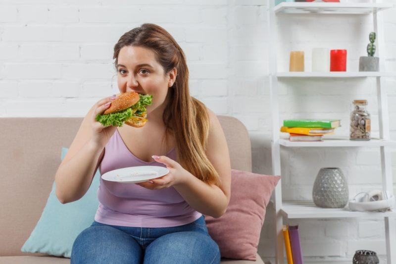 太っている女性がハンバーガーを食べているとこ
