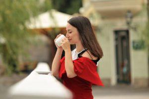外で温かい飲み物を摂る赤い服の美女