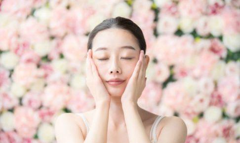 バラに囲まれ手を頬に持っていってうっとりしている女性