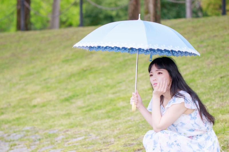 日傘を差して紫外線対策をしているロングヘア女性