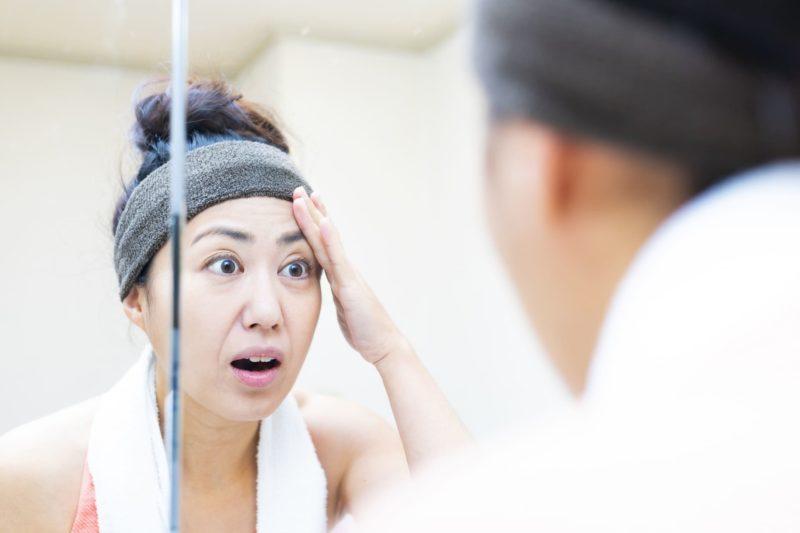 洗顔後に鏡を見て唖然とする女性