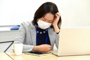 デスク作業中に頭を抱える女性