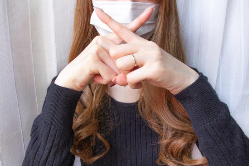 マスクの前で×マークを作る女性