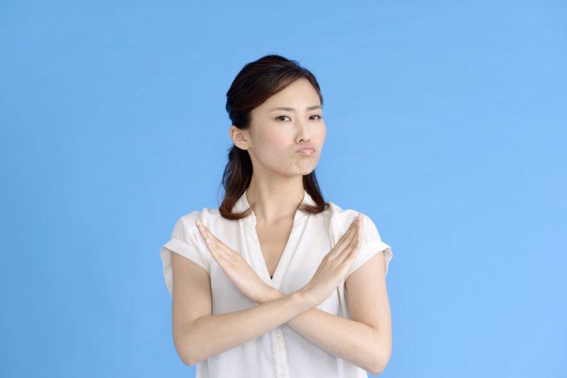 青い背景の中しかめ面してバツを示している女性