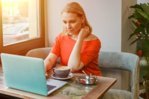 西日が差し込む部屋でパソコン作業をしているオレンジニットの女性
