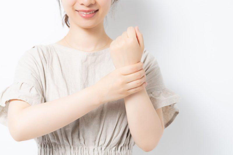 左手首を握っているワンピース姿の女性の上半身