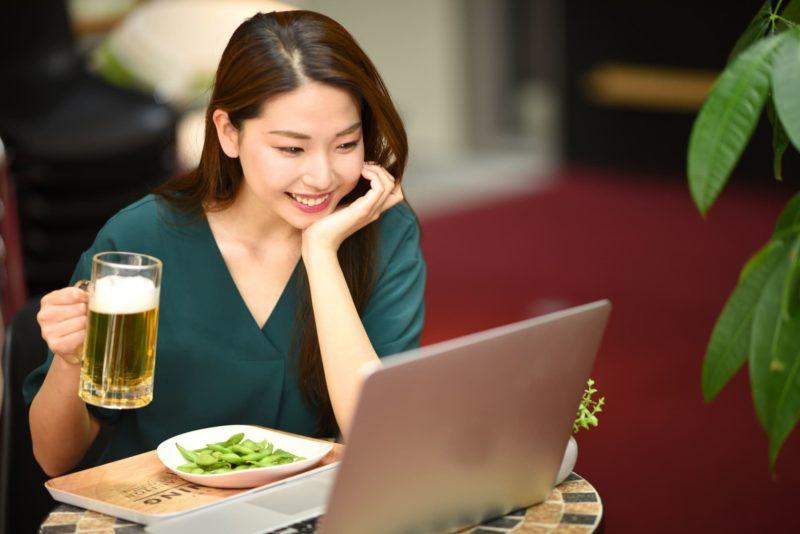 ビールと枝豆でオンライン飲み会をしている女性
