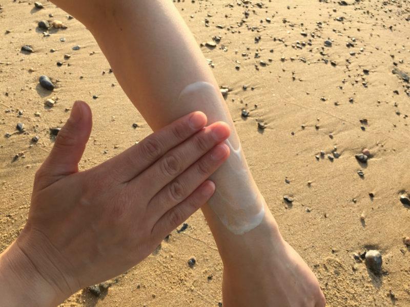 砂浜で左腕を念入りに日焼け止めを塗っているところ