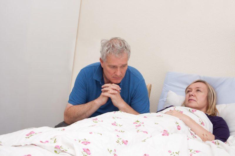 病弱な妻を看病し祈っている夫