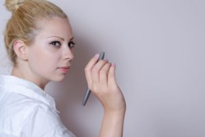 後ろの壁に何か特殊なペンで書こうとしている女性