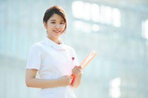 日の当たる背景の中で微笑む若い看護師