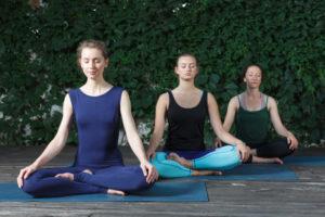 茂みを背景にみんなで座禅ヨガをする外国人女性