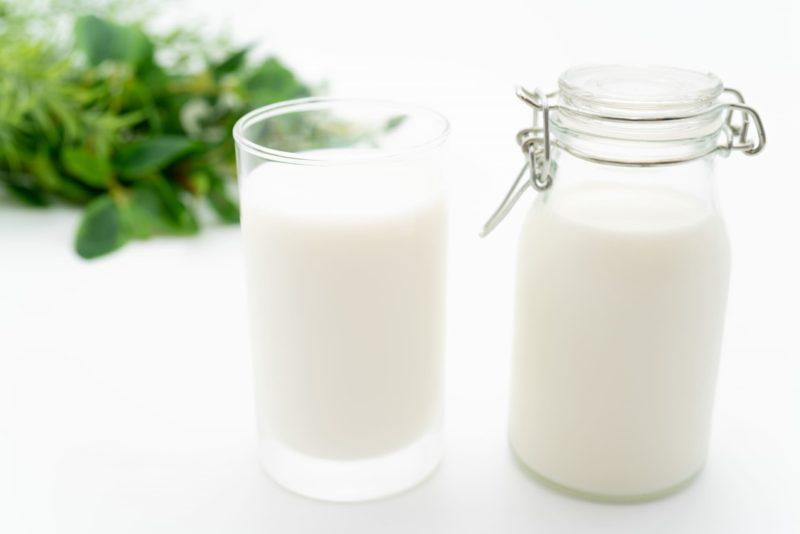 瓶の牛乳とコップ1杯いっぱいの牛乳