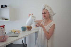 頭にタオルをぐるぐる巻きにしてお茶を飲んでいる女子