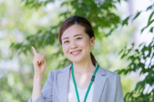 木陰に人差し指を指し示す女性会社員