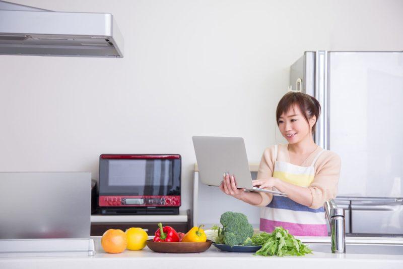 ノートパソコンでレシピを見ながら夕飯を作ろうとしている女性