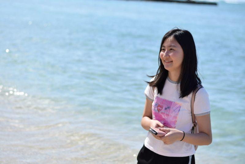 きらめく海にいるリュック背負った女性高生
