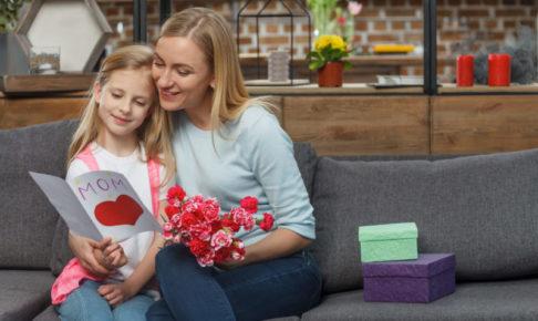 広そうなリビングのソファで小さな子供と絵本を読んでいる外国人ママ