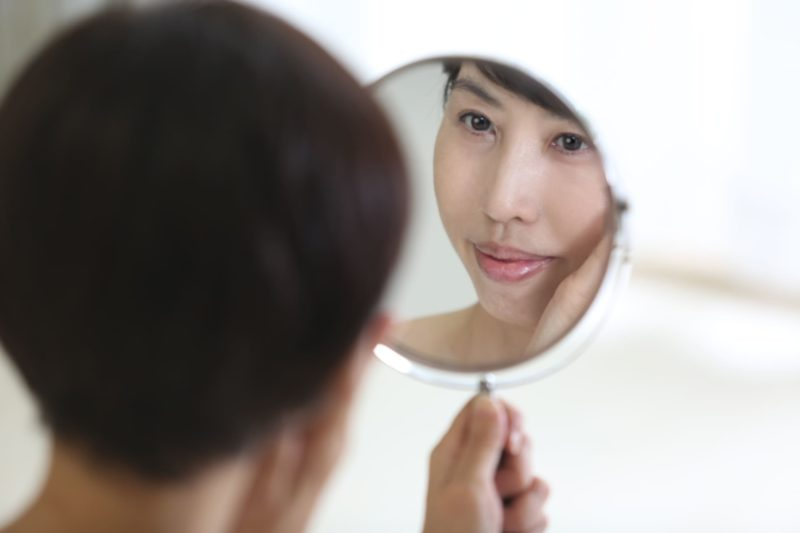 自分の顔を鏡で真剣に見つめるご婦人